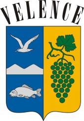 """Velence címere: álló, csücskös talpú téglapajzs kékkel és arannyal osztott jobb oldali mezejének közepén ezüsthegy két csúccsal, felette jobbra repülõ ezüstmadár, az alsó részben lebegõ, jobbra fordult ezüsthal, a bal oldali aranymezõben zöld ágon zöld levéllel, lebegõ zöld szõlõfürt. A pajzs felett """"VELENCE"""" felirat."""